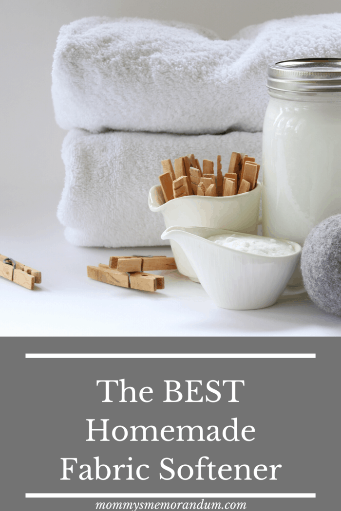 white fluffy towels folded with clothes pins, wool dryer balls and homemade fabric softener in large mason jar