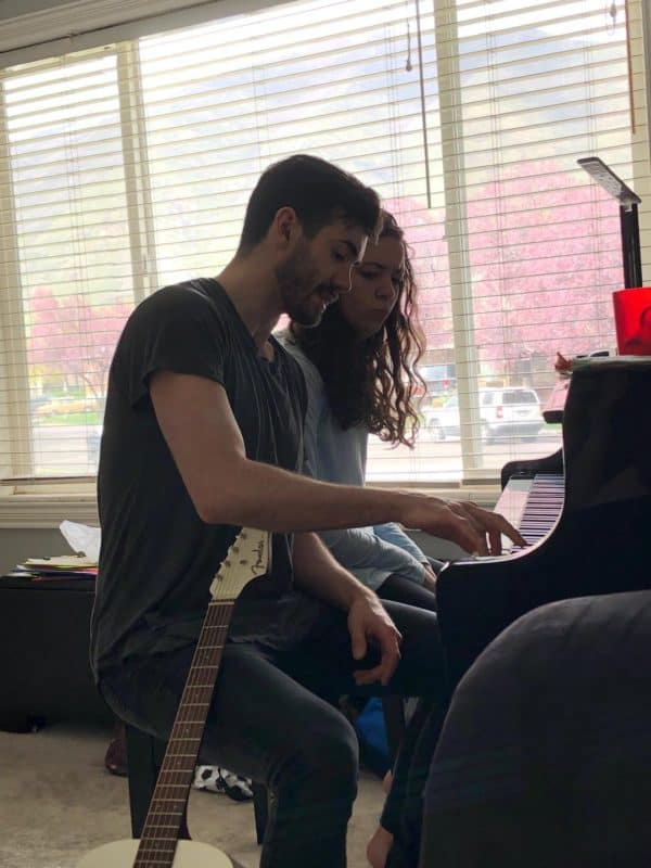 young man giving piano lessons to young woman