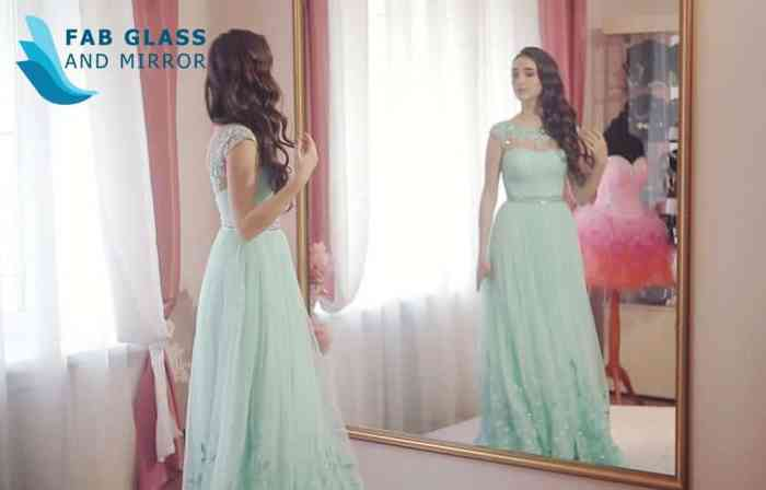 woman in mint green formal admiring herself in full length mirror