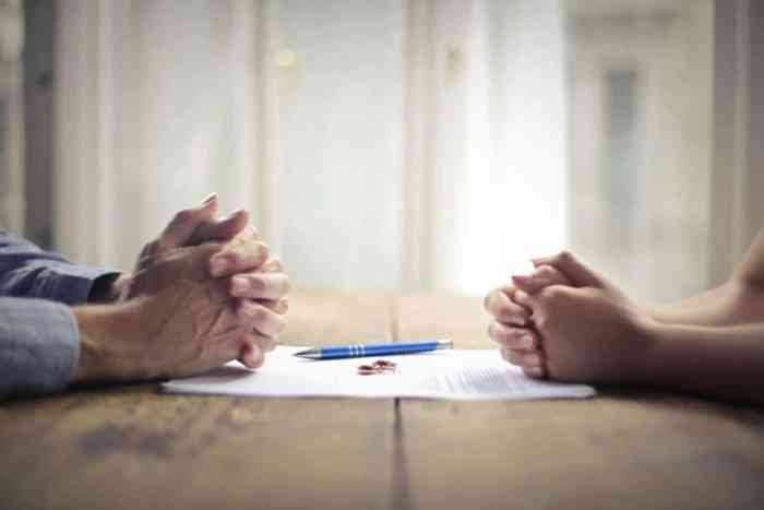 couple coping with divorce wedding rings on divorce papers iwth pens