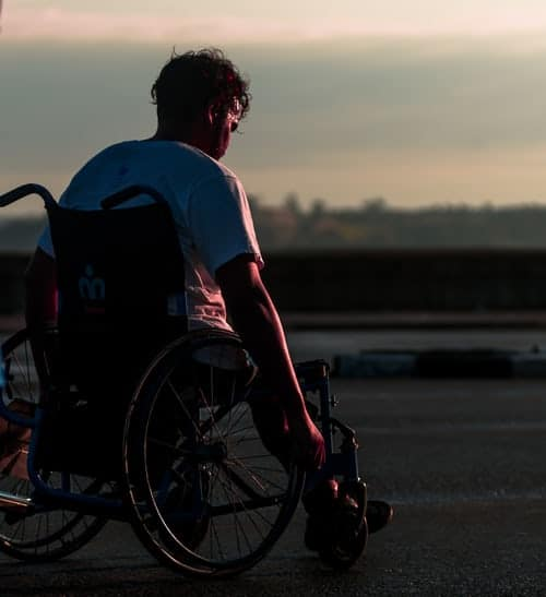 man in electric wheelchair watching sun set