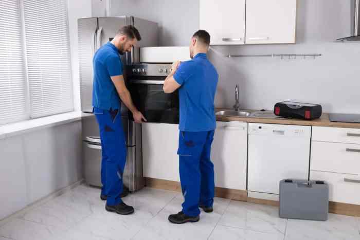repairmen doing appliance repair on oven
