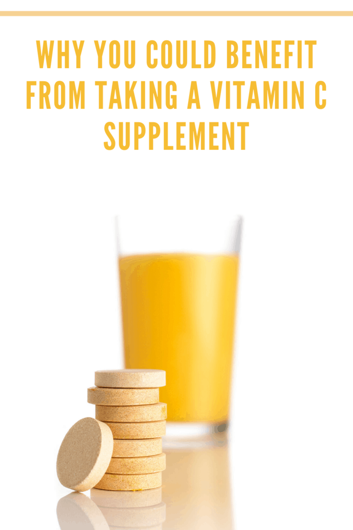 glass of orange juice with vitamin c supplements stacked in front