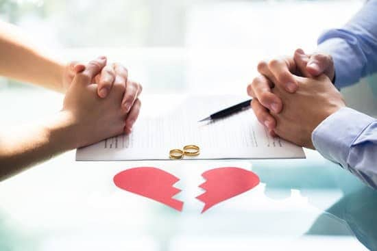 man and woman sitting across from each other, hands on table, paper heart broken and wedding rings on table.