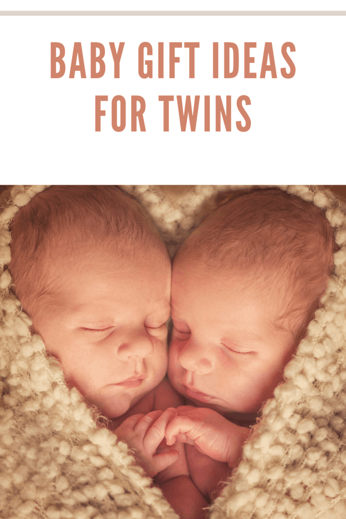 twin baby wrapped in beige blanket. The blanket is postitioned as a heart with only their faces in the heart.