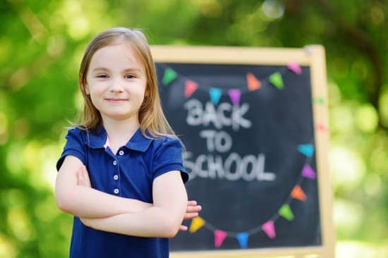 girl starting school standing next to back to school written on chalkboard