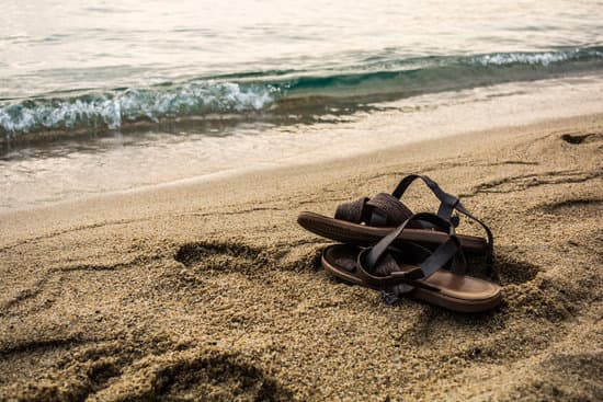 Pair of leather brown sandals on a sundy beach near the sea
