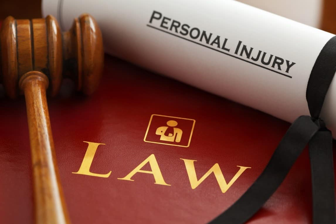 "maroon law book with mallet on top and rolled up paper with ""personal injury"" typed on paper"