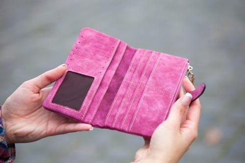 empty pink wallet opened in woman's hands