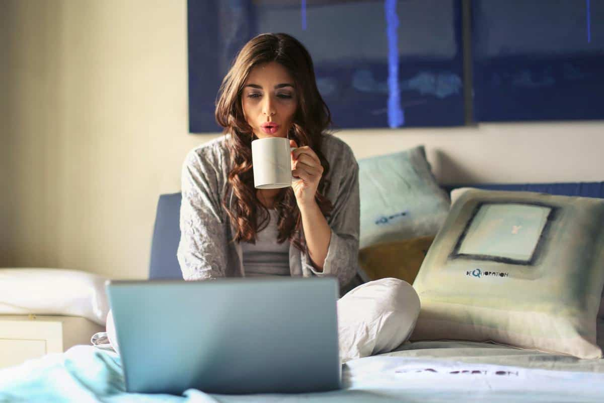 woman in pajamas sitting on bed, drinking coffee, with computer making money working from home as a stay at home mom