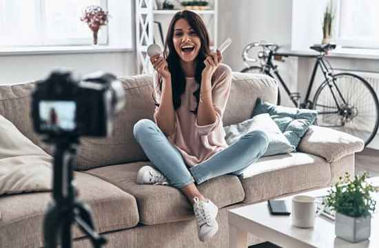 Beautiful young woman holding beauty products and smiling while making social media video