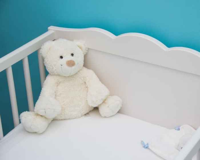 white teddy bear in white crib with teal wall