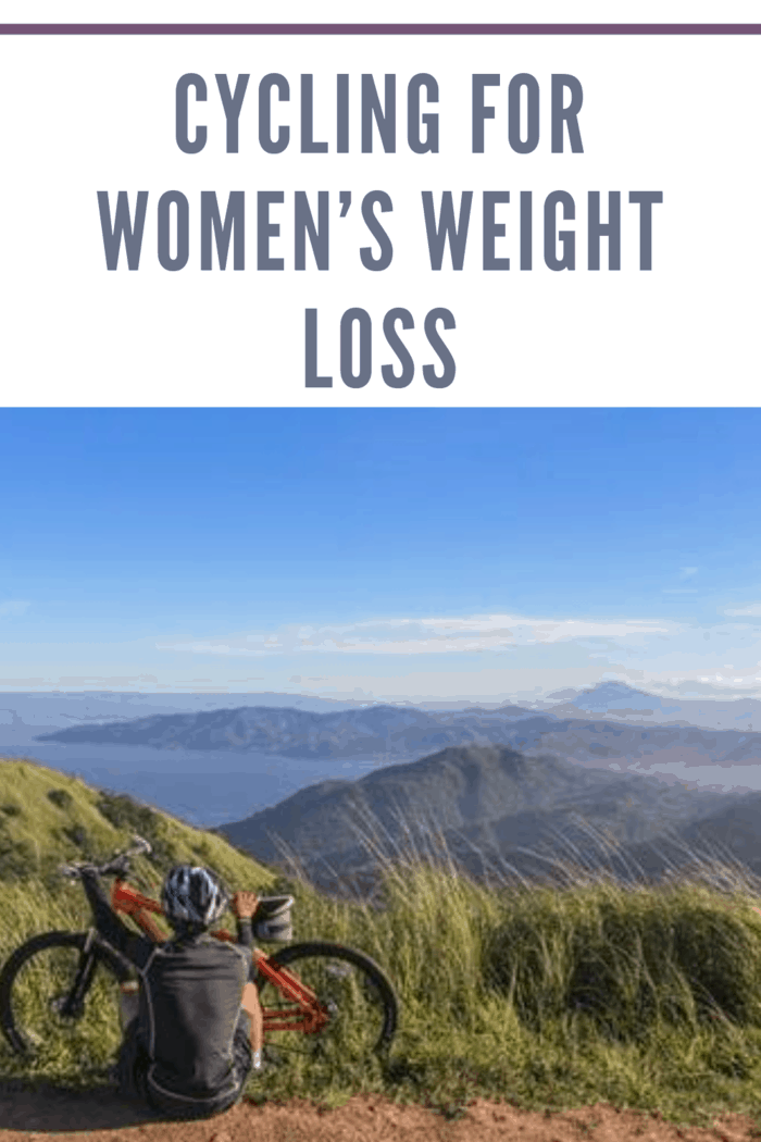 woman resting at top of hill after cycling to enjoy the scenic view of mountains