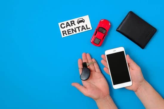"Car rental app concept. Toy car, auto drive license, human hand with smartphone and car key, text sign ""CAR RENTAL"" on blue background. Flat lay composition. Top view."