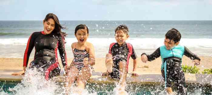 mom and kids splashing in water at beach