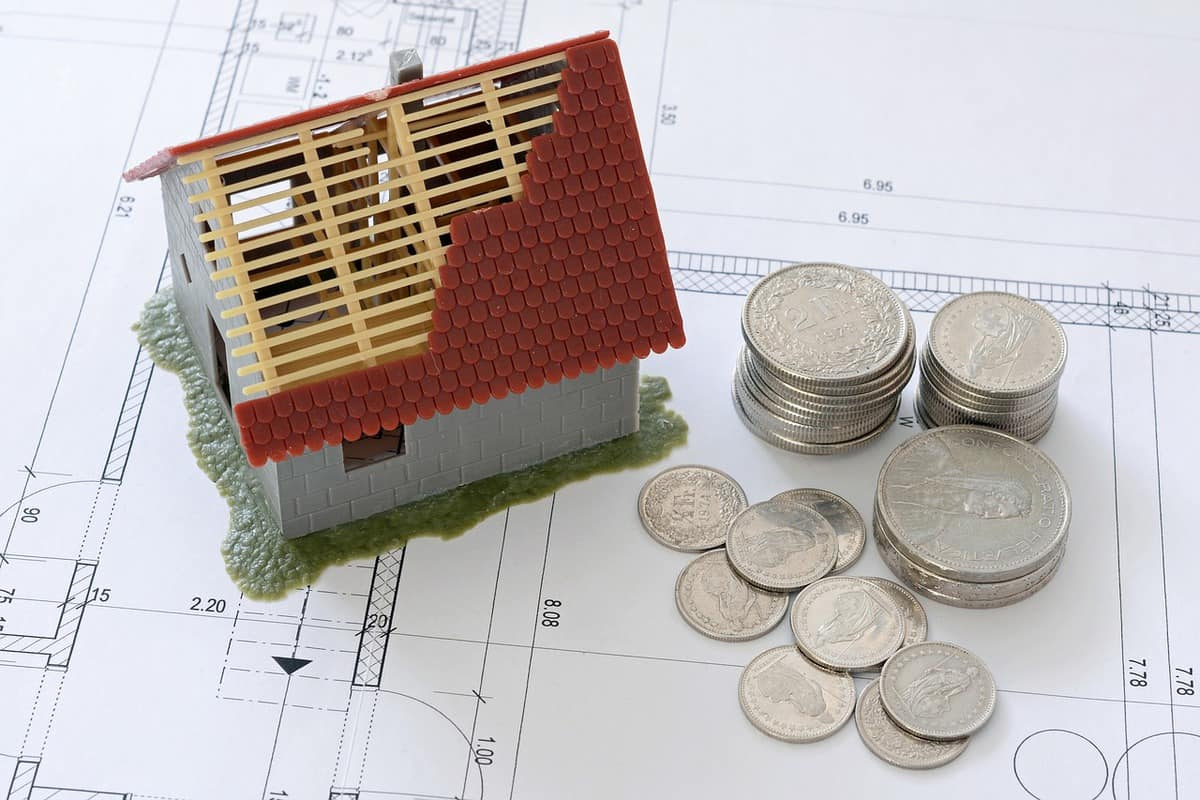 model of house with damaged roof and stacks of silver coins next to it