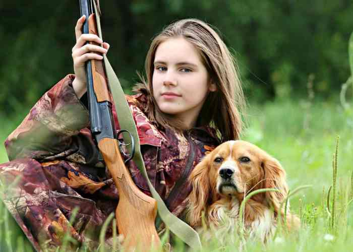 young woman hunter with gun and dog
