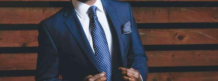 torso of man in nice suit with navy tie
