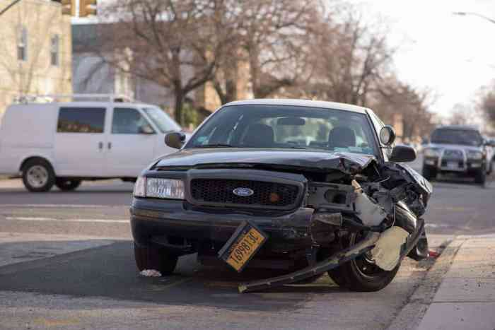 wrecked car on street with license plate hanging off bumper