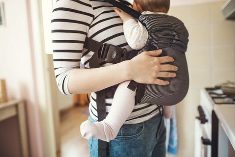 woman in striped shirt with baby in baby carrier