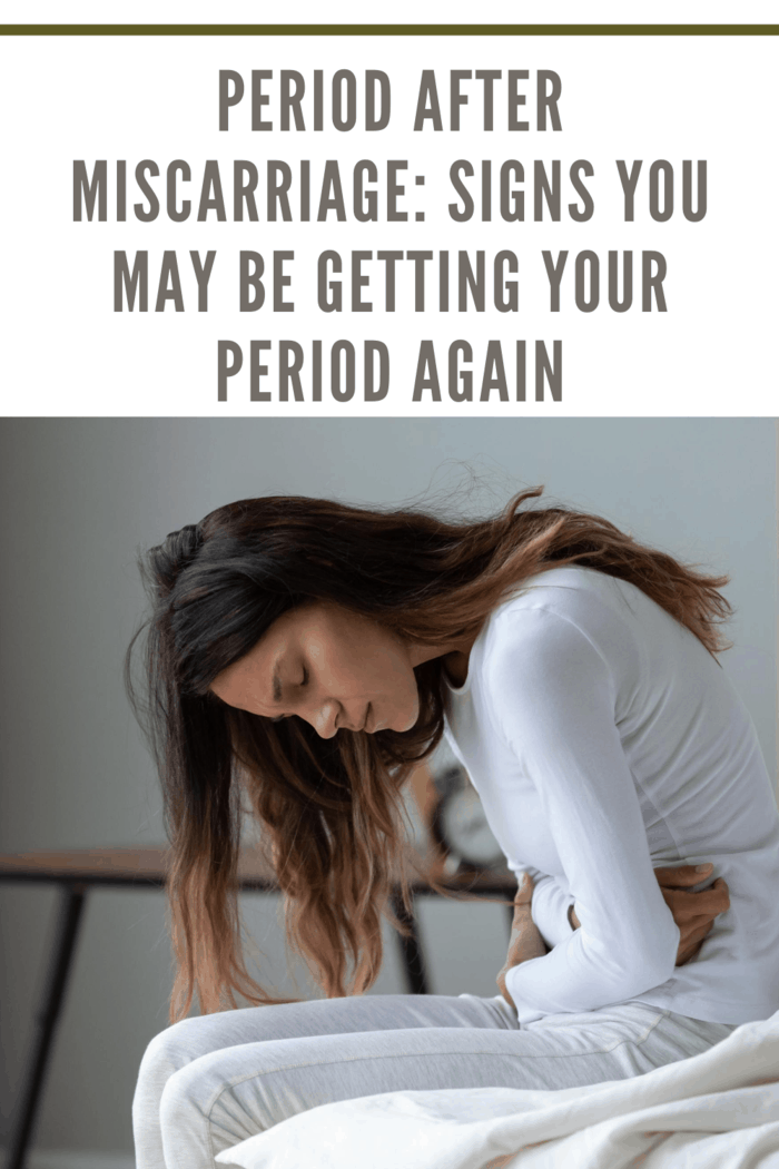 woman in bed with mentstrual pains from first period after miscarriage
