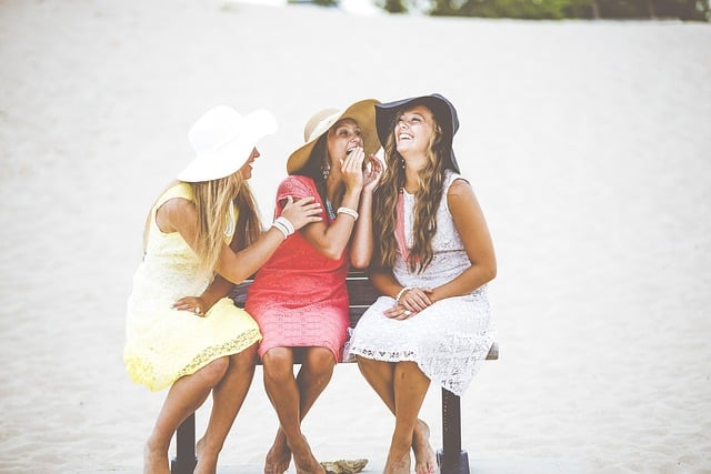 girlfriends with hats, sitting on a bench dressed in summer fashion