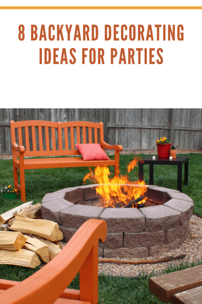 A charming back yard fire pit, surrounded by brightly colored orange chairs and benches. Around the flaming fire pit is a bright colored pillow, flower pots, and a pile of split wood, waiting to be burned. In the background is a weathered fence. Colors of