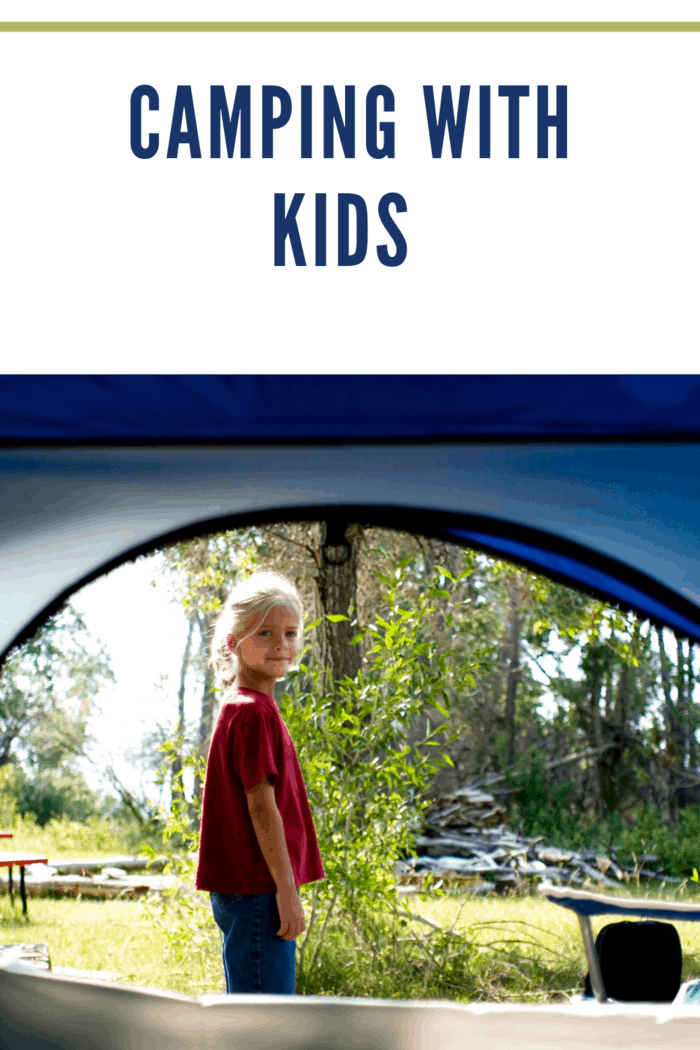 A young girl outside her tent.