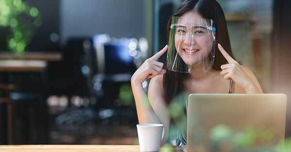 Pretty woman wearing face shield for healthcare, Young Asian woman sitting in coffee shop and working on laptop