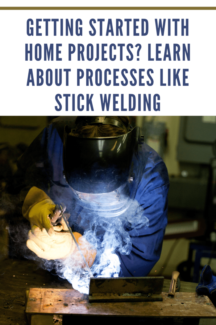 Industrial worker stick welding plate metal
