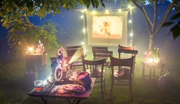 Small cinema with retro projector in summer garden for backyard theme party