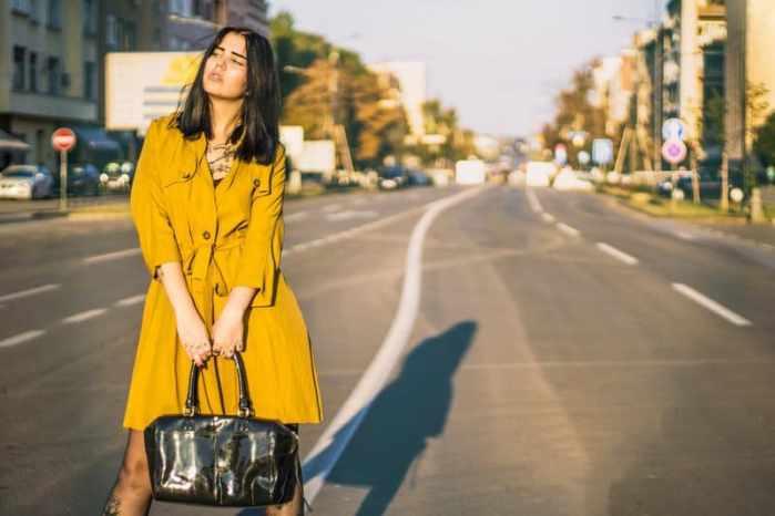 Woman Standing On Road Holding Leather Handbag