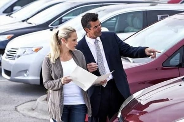 dealer walking car lot with woman interested in buying a pre-owned car