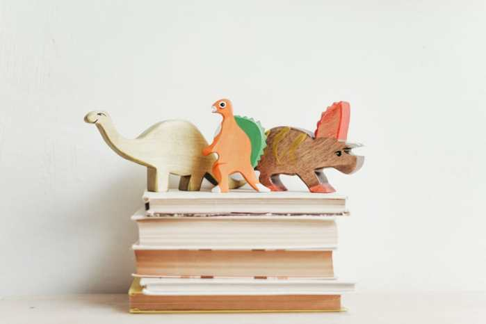 wooden dinosaurs on top of four dinosaur books you must read