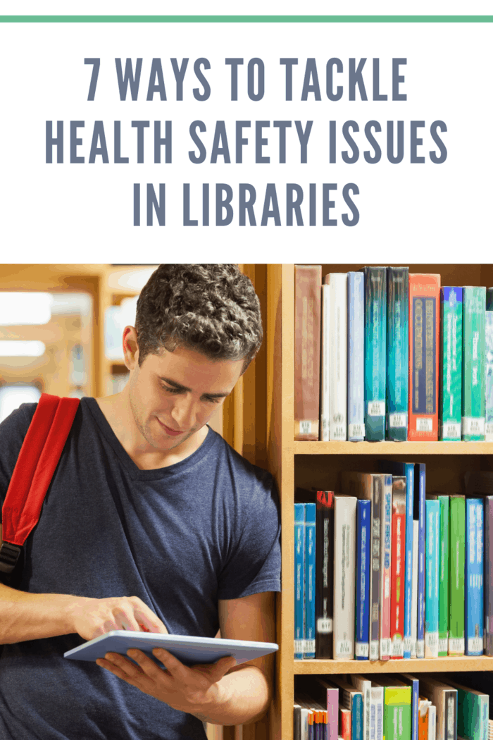 Student leaning against bookshelf holding a tablet pc at the library practicing safety issues