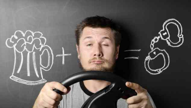 Man against the chalkboard holding a steering wheel, drawing of a beer mug and handcuffs representing florida drivers drug and alcohol course