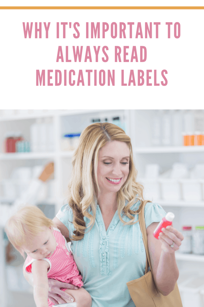 Mid adult Caucasian woman is mother shopping for cold medicine while holding her toddler daughter in local pharmacy. Mother is reading medication label while holding baby.