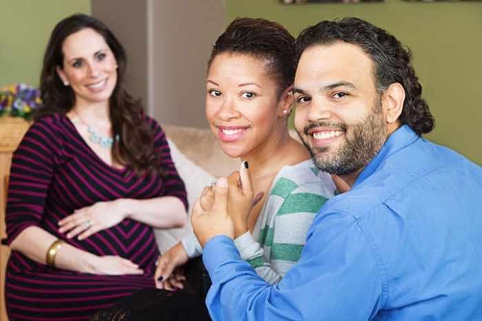 Smiling Hispanic couple sitting with beautiful surrogate mother