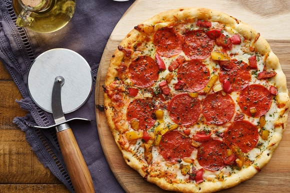 pepperoni pizza on wooden serving tray with cutter flat lay composition