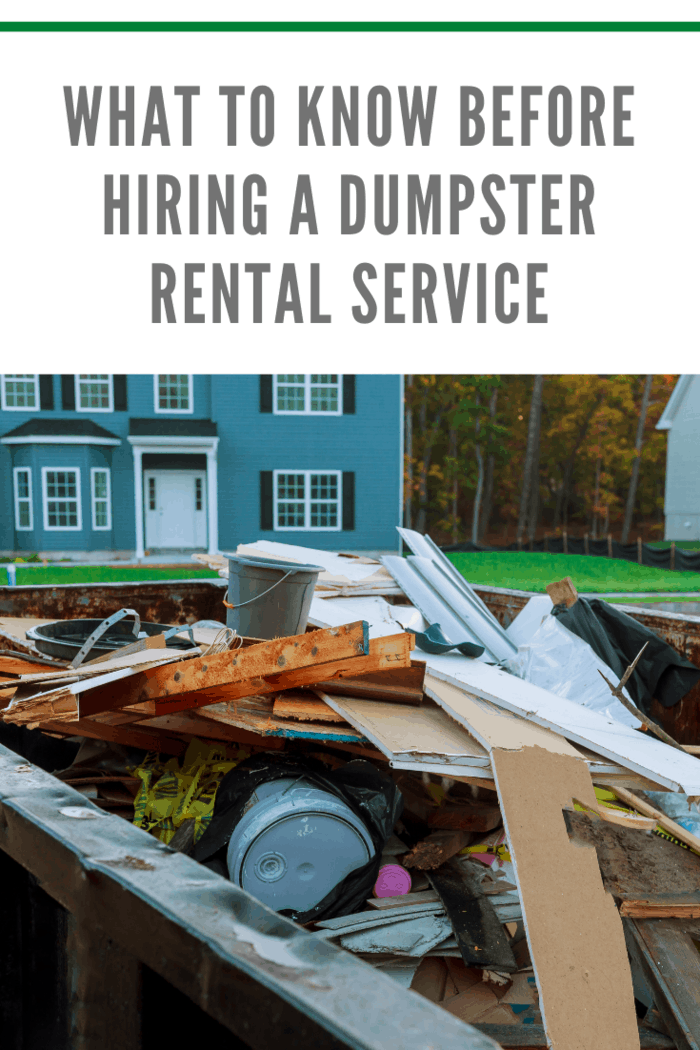 dumpster rental filled with debri in front of two story home