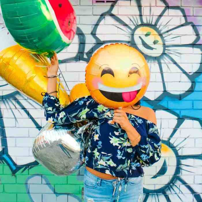 woman making a positive impact with her clothes using emoji mylar balloon for her face