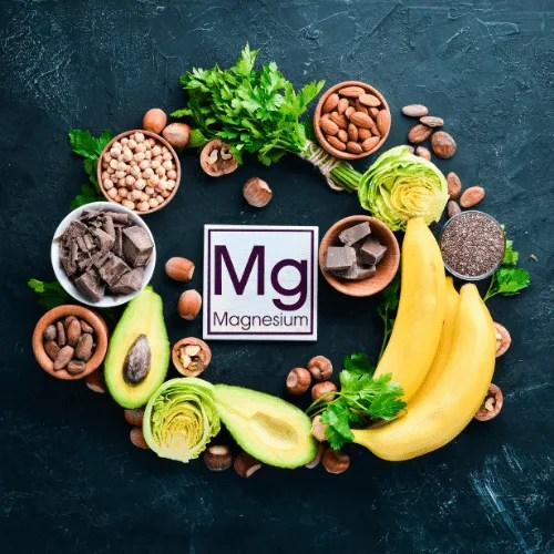 Foods containing natural magnesium. Mg: Chocolate, banana, cocoa, nuts, avocados, broccoli, almonds. Top view. On a black background.