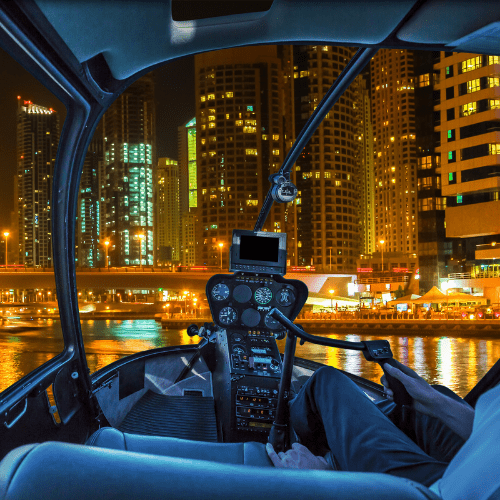 Helicopter cockpit flies in Dubai Marina by night, United Arab Emirates, with pilot arm and control board inside the cabin.