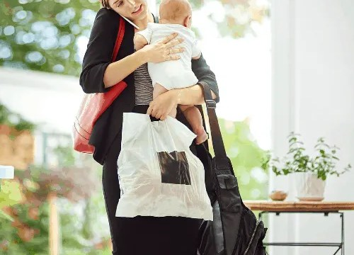 Shot of a busy businesswoman carrying a shopping bag and her baby while talking on the phone on her return from work