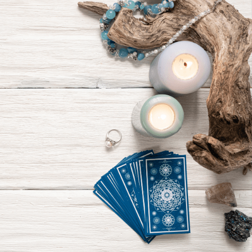 Blue tarot cards on white wooden table background.