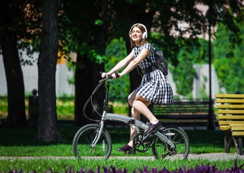 Young woman rides bicycle in the park