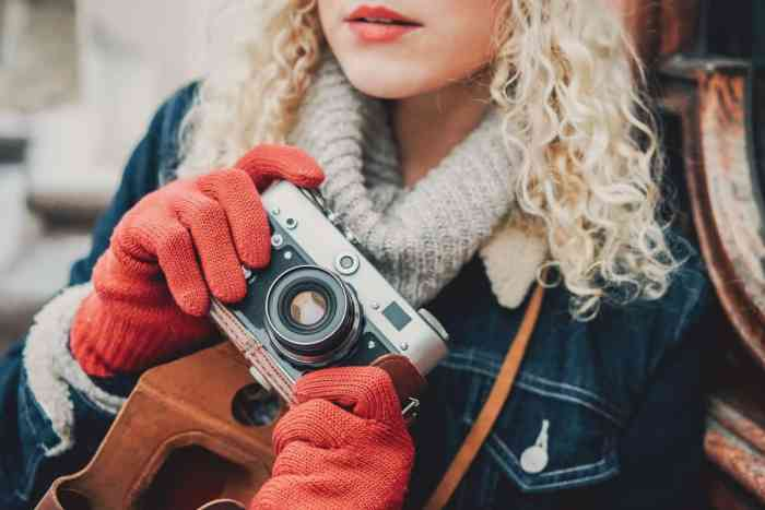 Old Film Camera in the hands of a curly headed girl