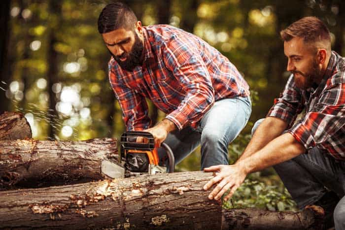 Two-Lumberjacks-sawing-wood-trunk-with-big-chainsaw