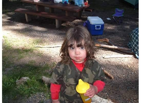 little girl camping with sippy cup of water
