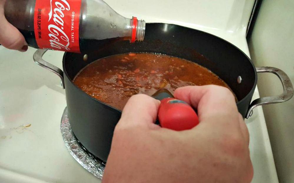 coca cola chili recipe stirring in the tomato sauce